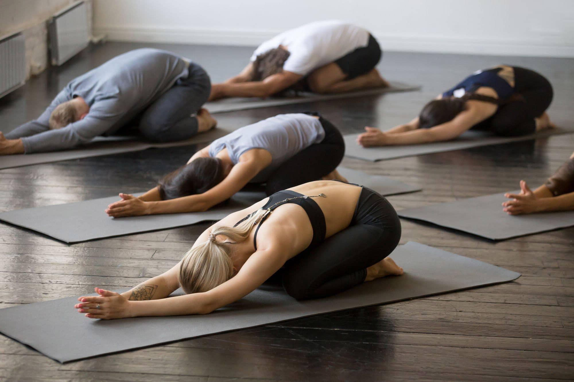 Grupo de personas haciendo Balasana en estudio de Yoga