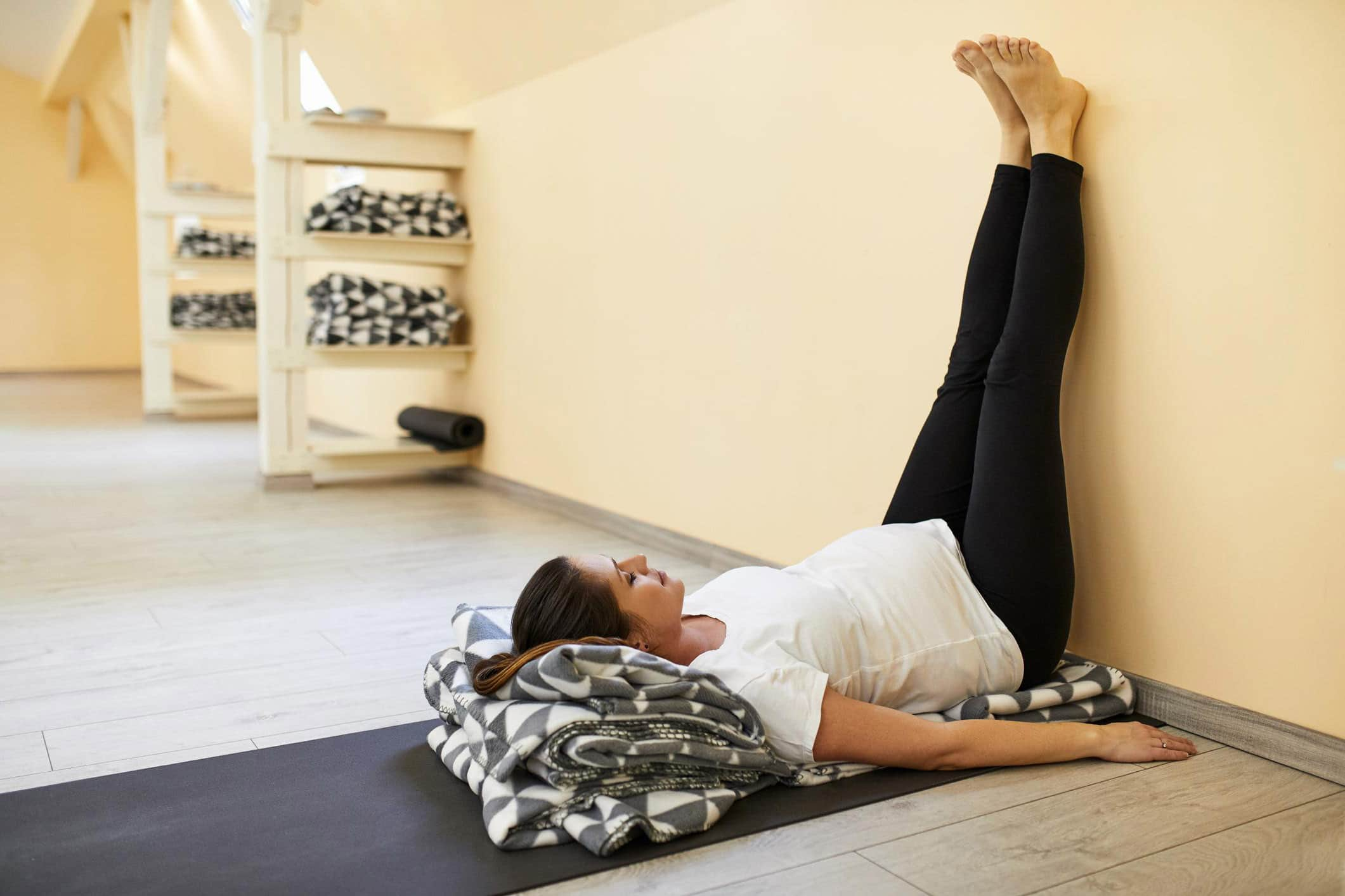 Chica haciendo Viparita Karani en estudio de yoga