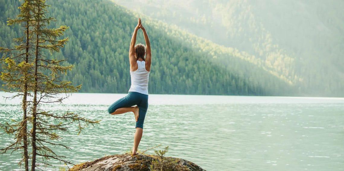 Chica haciendo la postura del arbol en un lago
