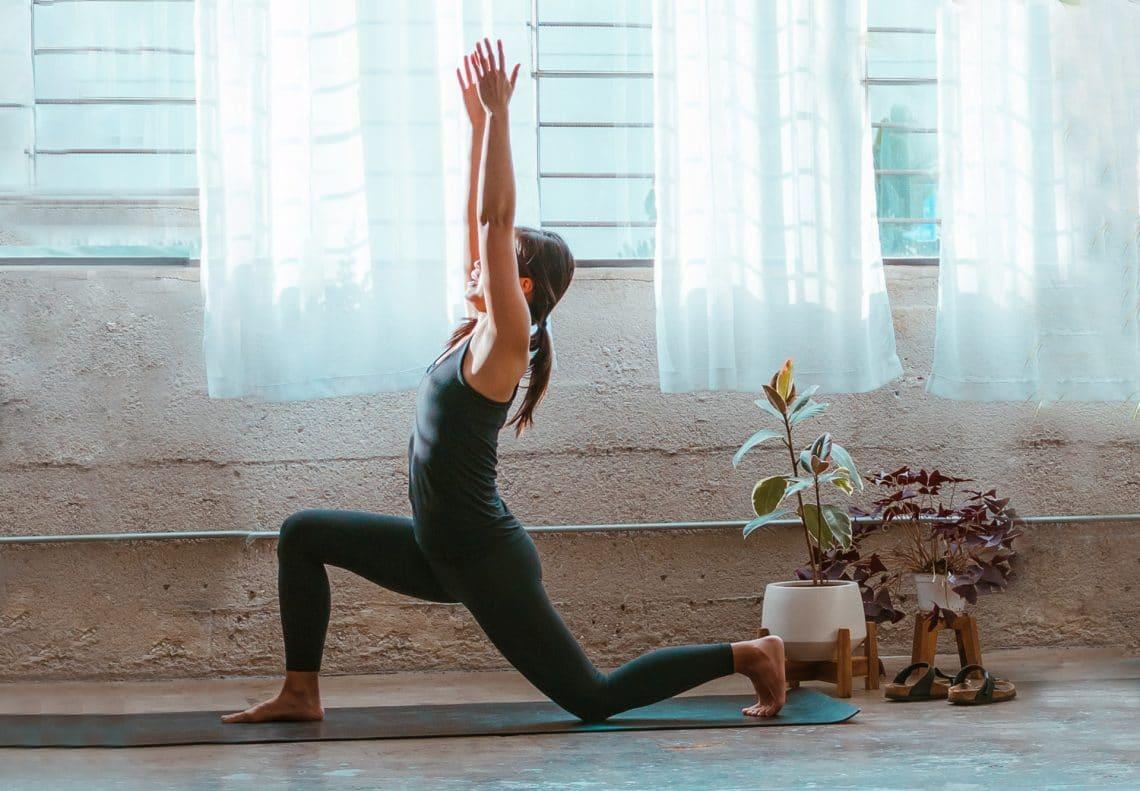 Chica en estudio de yoga haciendo la postura de Anjaneyasana o postura de la luna creciente