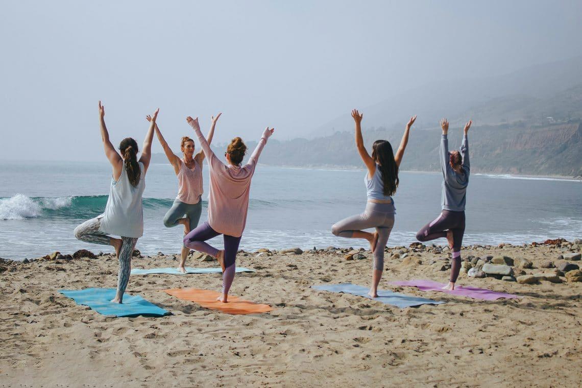 Chicas practicando Iyengar yoga en la playa