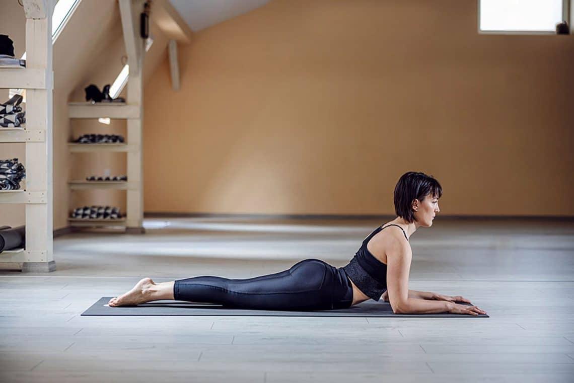 Chica haciendo la postura de yoga de Salamba Bhujangasana postura de la esfinge